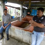 Two men at a coffee and washing station