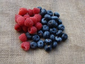 Composition of raspberries and blueberries photographed on a coffee sack